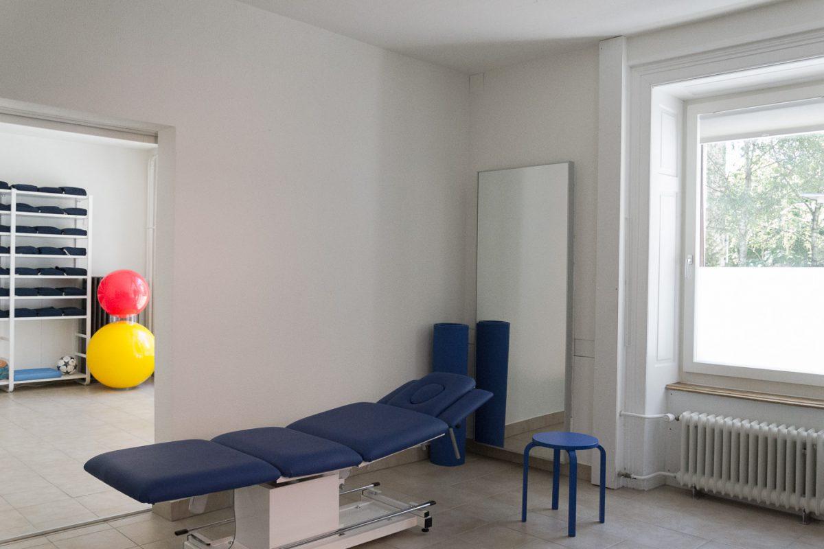 Eine blaue Behandlungsliege steht in einem hellen, weissen Raum. Ein blauer Hocker und ein Spiegel sind im gleichen Raum. Das Fenster zeigt auf Bäume und Häuser. Im angrenzenden Raum sind ein gelber und ein roter Gymnastikball zu sehen und ein Regal mit Handtüchern.