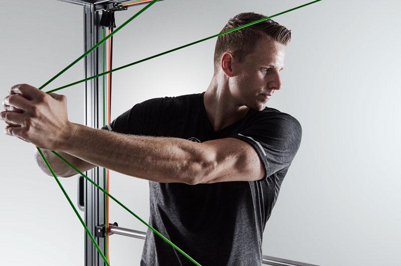 Ein Sportler trainiert seine Arme in einem Sportgerät